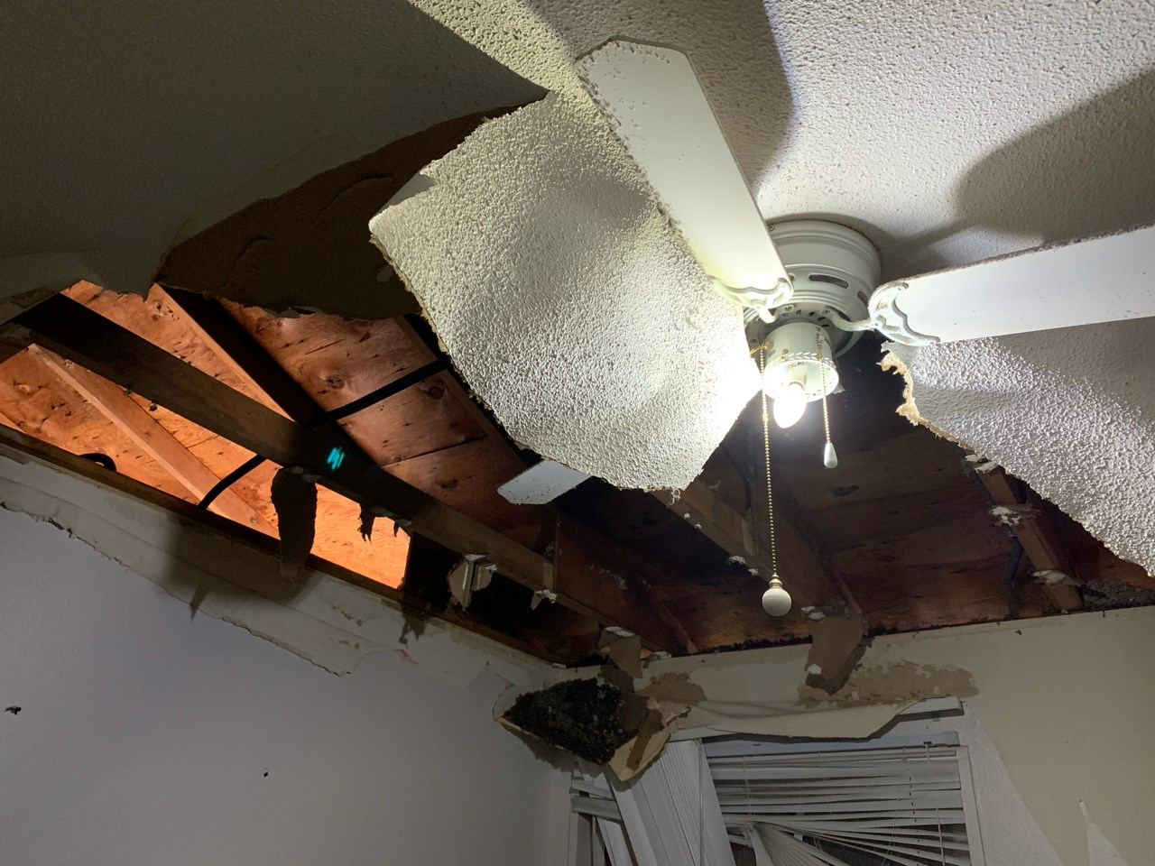 Partially collapsed townhouse ceiling and ceiling fan